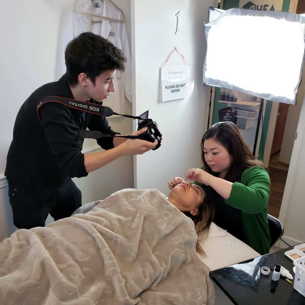 Aze wearing black taking pictures and videos of an eyelash extension treatment.