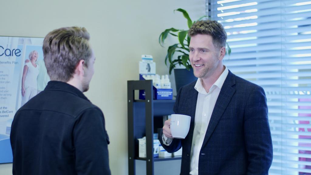 Keenan Beavis of Longhouse speaking with Scott Hyde of Fraser Valley Beltone while Scott drinks coffee