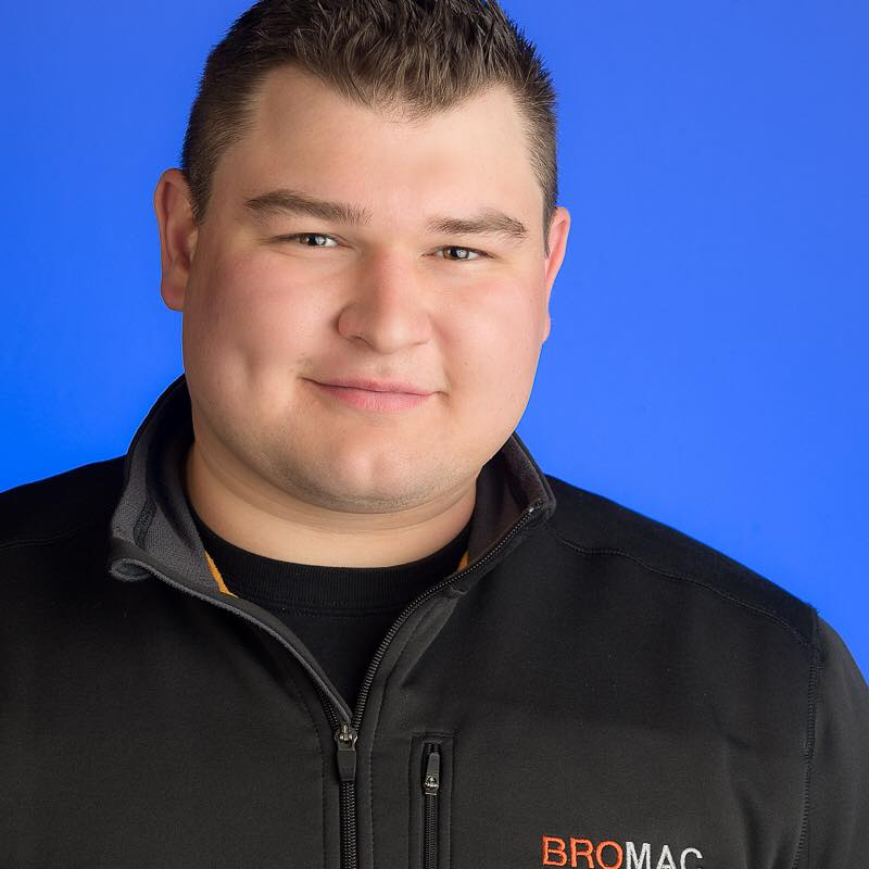 Photo of Brody Mcintosh the founder of Bromac Mechanical, a local plumbing company in Abbotsford.  He is standing in front of a blue background.