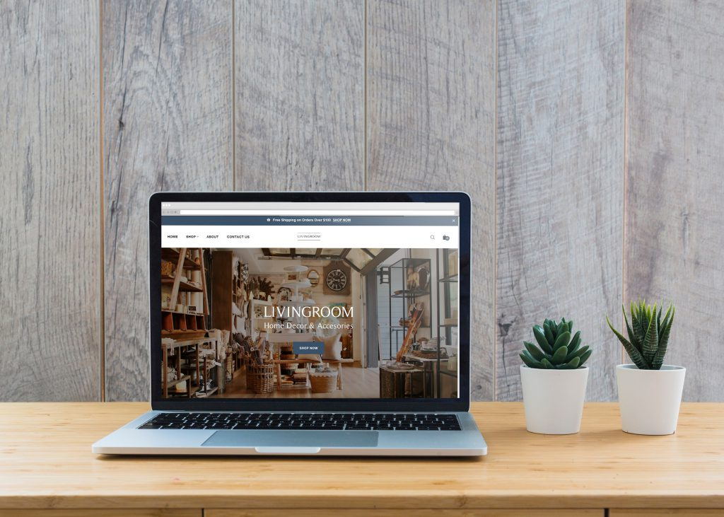 LivingRoom Fort Langley website mockup on a wood table, granite backdrop and beside two cactuses