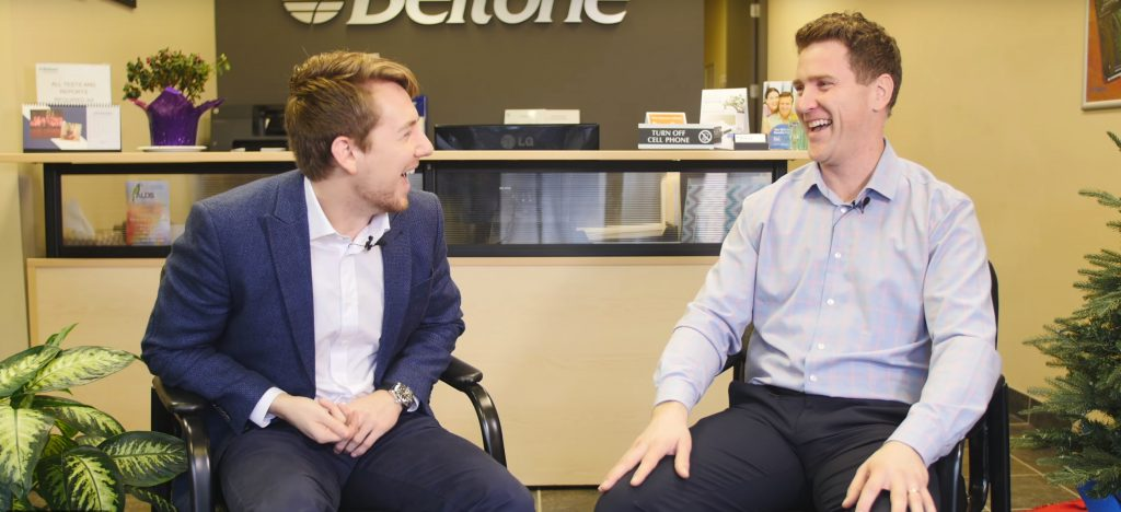 Keenan Beavis and Scott Hyde from Fraser Valley Beltone sitting in front of the Beltone logo laughing.